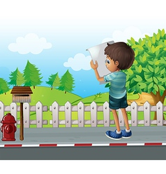 A boy with a paper standing near the fence at the vector image