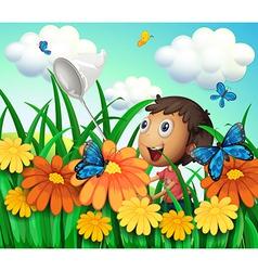 A boy catching butterflies at the flower garden vector image