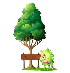 A green monster crying beside the empty wooden vector image vector image