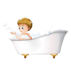 A boy playing at the bathtub while taking a bath vector image vector image