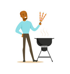 Smiling african man preparing meat kebabs on a vector