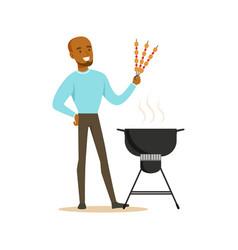 smiling african man preparing meat kebabs on a vector image vector image