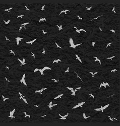 Flying birds silhouettes on black grunge vector