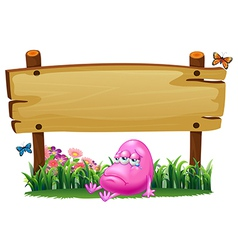 A pink beanie monster under the empty wooden vector image vector image