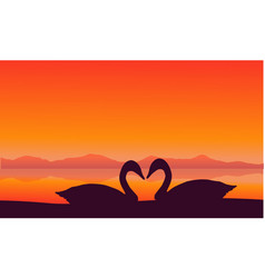 Silhouette of two swan at sunset scenery vector