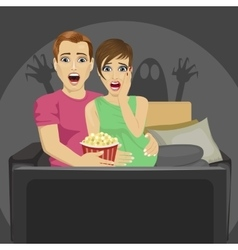 Young couple watching horror movie at home vector