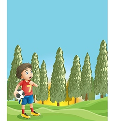 A young boy holding a soccer ball near the pine vector image vector image