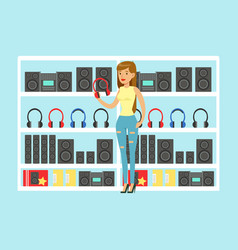 Young woman choosing headphones at tech store vector