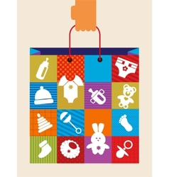 Hand holding baby shopping bag with toy and cloth vector