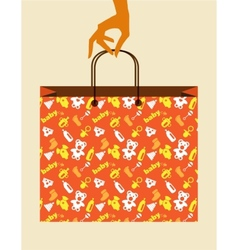 hand holding baby shopping bag with toy and cloth vector image