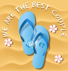 A pair of light blue flip flops on sandy beach vector