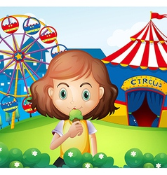 A girl at the carnival eating an icecream vector image