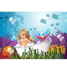 A bathtub under the sea with a mermaid vector
