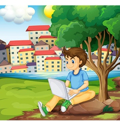 A young boy using the laptop under the tree at the vector image vector image