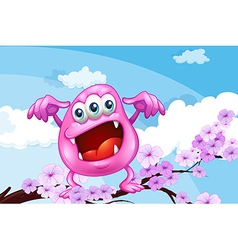 A pink beanie monster above the branch of a tree vector