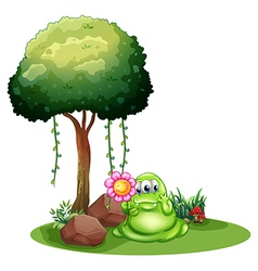 A monster holding a flower standing near the tree vector image