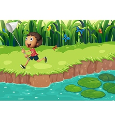 A boy catching butterflies at the riverside vector image