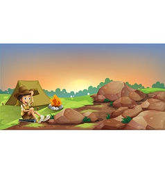 A young boy camping near the rocks vector