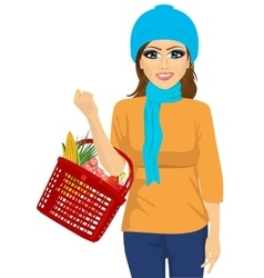 Smile woman holding a shopping basket full of food vector