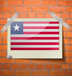 Flags liberia scotch taped to a red brick wall vector