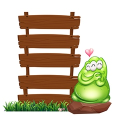 A green monster beside the empty wooden boards vector image