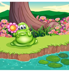 A green monster at the riverbank holding a flower vector image