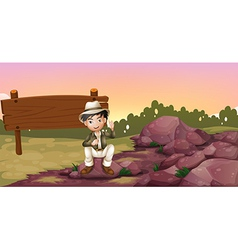 A boy sitting on a rock near an empty signboard vector image vector image
