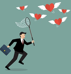 Businessman trying to catch hearts flying vector image