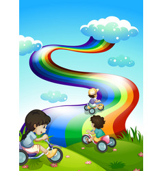 Kids playing at the hilltop with a rainbow in the vector image