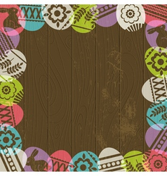 Wooden background with frame of easter eggs vector