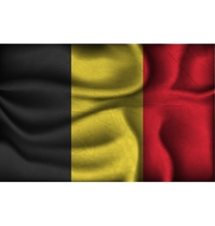 Crumpled flag of belgium on a light background vector