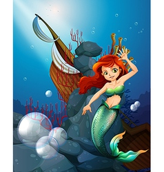 A sea with a mermaid near the wrecked boat vector image vector image