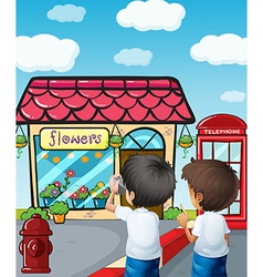 Two boys taking photos near the flower shop vector image vector image