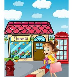 A girl near the flowershop holding a bag and a vector
