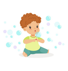 Adorable little boy sitting blowing bubbles vector