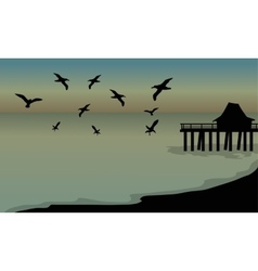 Silhouette of huts and bird at the beach vector