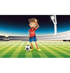 A boy with a soccer ball standing in the soccer vector image