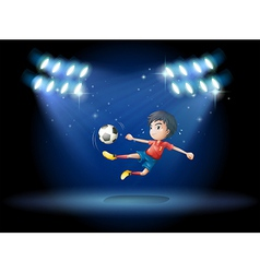 A young boy playing soccer with spotlights vector