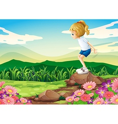 A young girl playing at the hilltop with rocks and vector