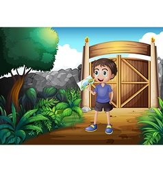 A boy holding a picture inside the gate vector