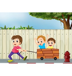Three boys playing near the wooden wall vector image