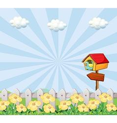 A bird at the birdhouse near the wooden fence vector image vector image