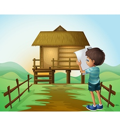A boy with a paper in front of the nipa hut vector