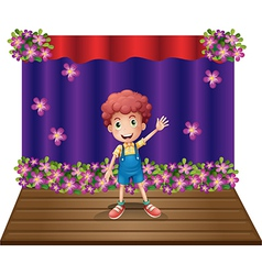 A stage with a young boy waving happily vector image