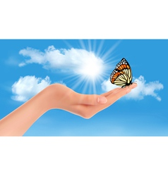 Hand holding a butterfly against a blue sky and vector