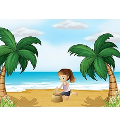 A young girl forming a sand castle at the beach vector