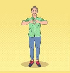 pop art handsome man showing heart hand sign vector image