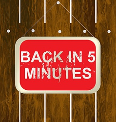 Back in 5 minutes sign hanging on a wooden fence vector image