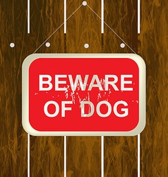 Beware of a dog sign on a wooden fence vector image