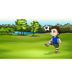 A boy playing soccer outdoor vector